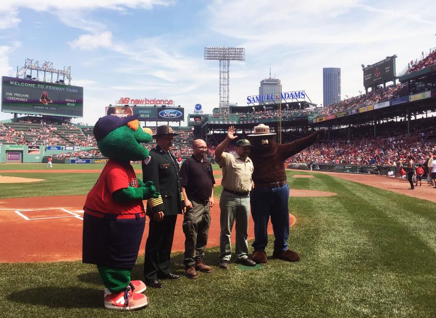 Smokey posing in the baseball field with other mascots and individuals