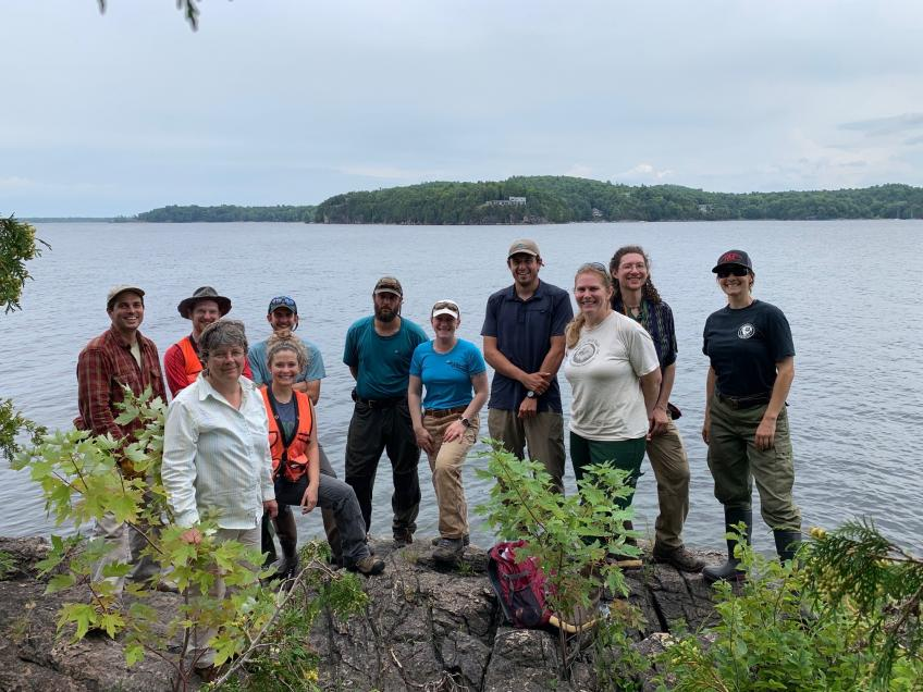 Group photo of volunteers standing in near the shoreline, lake behind, mountains in the far background