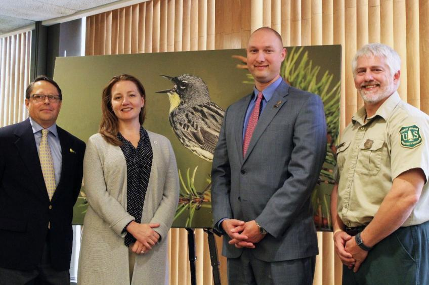 Three men and one woman standing in front of a photo of a bird