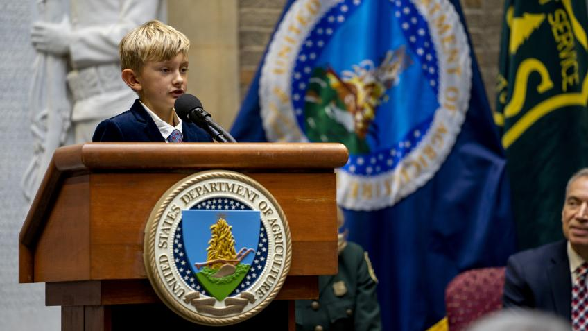 A picture of Asher Dean, New Mexico fourth grader and 2019 U.S. Capitol Christmas Tree Essay Contest winner, speaking at a podium about his essay during the annual USDA Christmas Tree Lighting Ceremony.