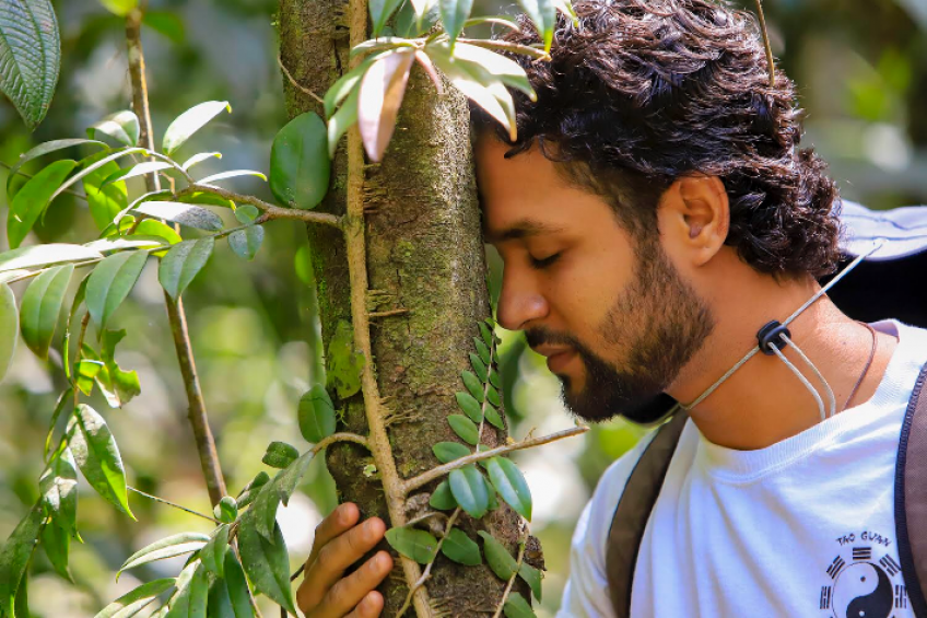 A picture of Ricardo Burke, Forest Therapy participant, shown here with his hand wrapped around a small tree.