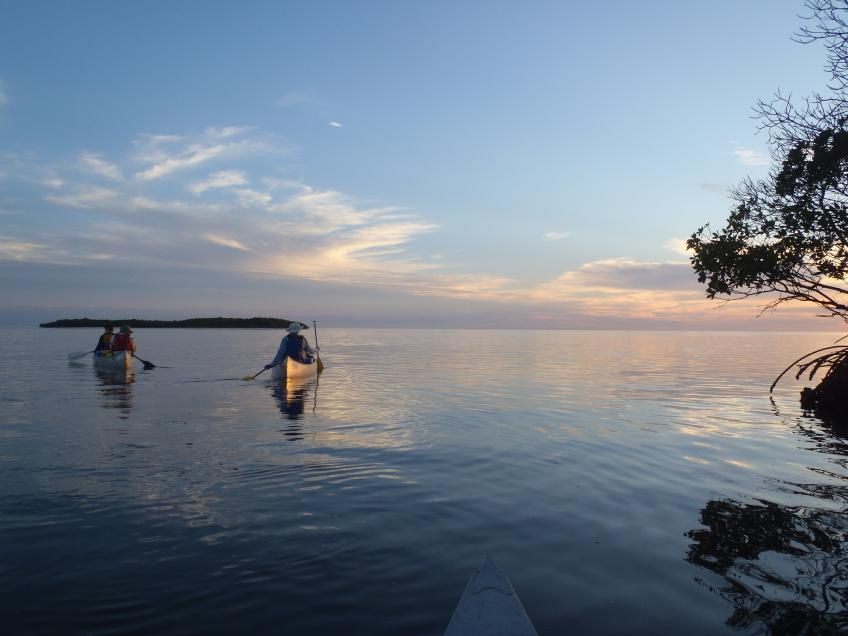 Veterans group canoeing at sunset.