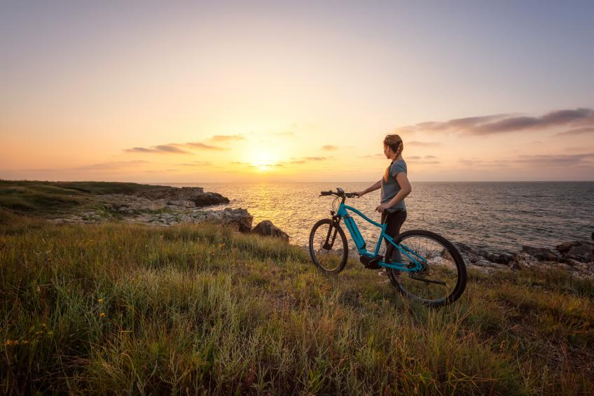 A picture of a woman standing next to an e-Bike in a grassy field next to a coastline with a sunset or sunrise in the horizon.