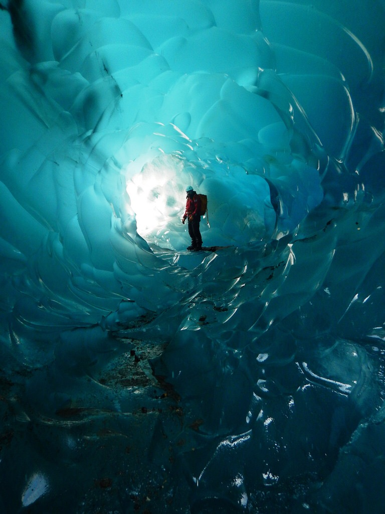 A photo of a A hiker stops inside the Mendenhall Glacier Caves, Tongass National Forest ()