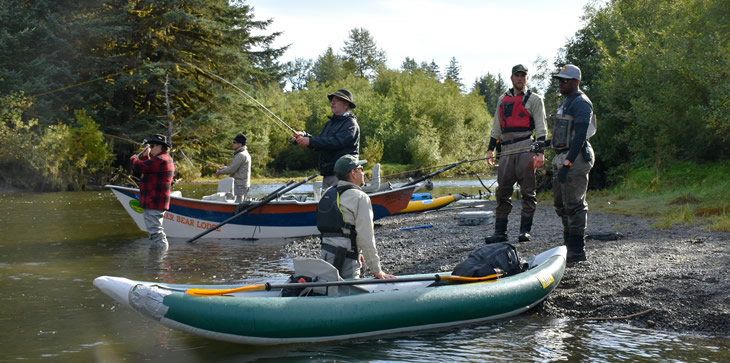 Tongass River Rangers speaking with a sport fishing guide while fishermen try to catch coho salmon in the Situk River of Yakutat, Alaska.