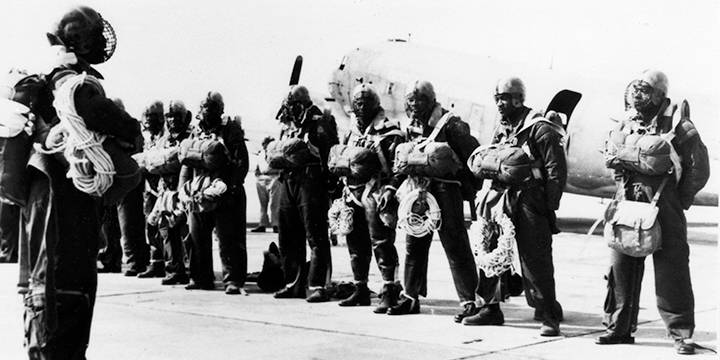 A picture of the Triple Nickel paratrooper unit lined up in front of an aircraft with their parachutes on.