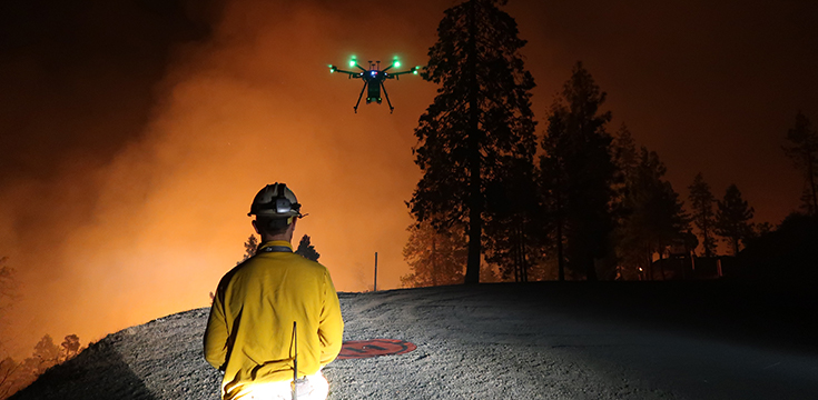 A picture of a firefighter using a drone near a wildland firefighter.